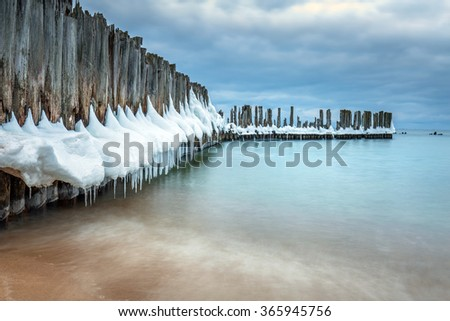 Frozen wooden breakwaters line to the world war II torpedo platform at Baltic Sea, Babie Doly, Poland - stock photo