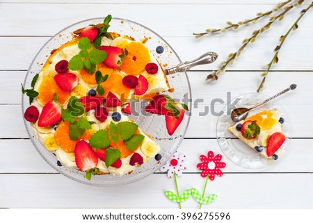 Fruit and berries cake on white wooden table, top view, easter, spring - stock photo