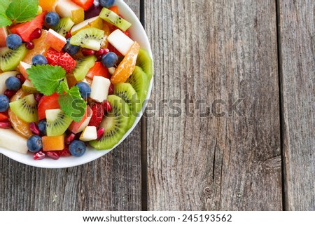 Fruit and berry salad and wooden background, horizontal, top view - stock photo