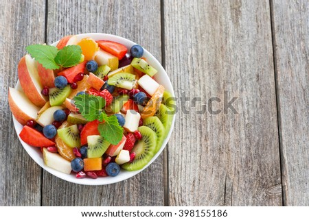 Fruit and berry salad on a wooden background, top view, horizontal