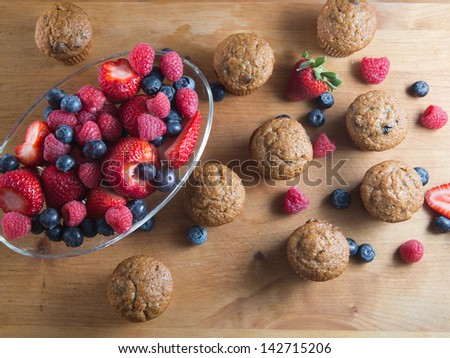 Fruit and bran muffins alongside bowl of fresh blueberries, raspberries and strawberries - stock photo