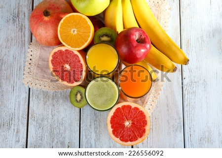 Fruit and vegetable juice and fresh fruits on napkin on wooden background - stock photo
