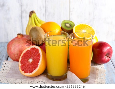 Fruit and vegetable juice and fresh fruits on napkin on wooden table on wooden wall background - stock photo