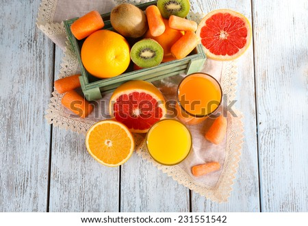 Fruit and vegetable juice and fresh vegetables and fruits on napkin and in wooden box on wooden background - stock photo