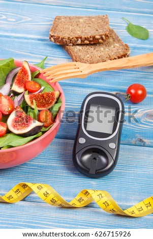 Fruit and vegetable salad, glucose meter for measurement sugar level and tape measure, concept of diabetes, diet, slimming, healthy lifestyles and nutrition