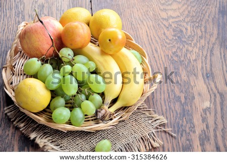 fruit basket on a wooden table - stock photo