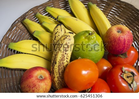 Fruit basket with persimmons, bananas, apples and tangerine