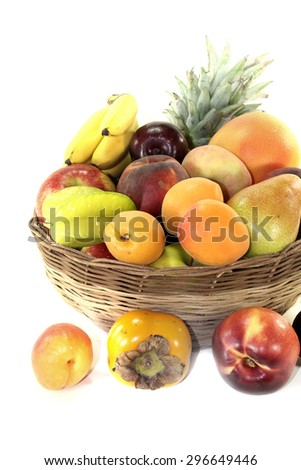 Fruit basket with various fruits on a light background - stock photo