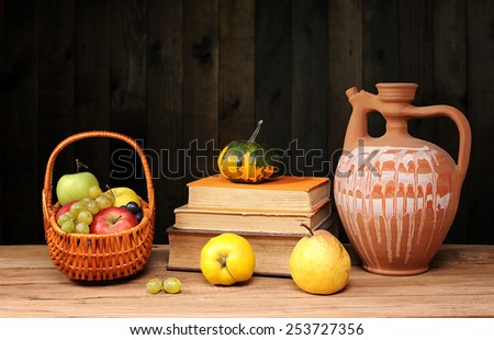 Fruit, books and ceramic carafe on the table - stock photo