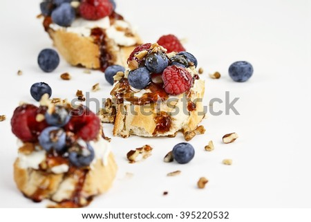 Fruit Bruschetta with cheese spread, fresh berries, walnuts and a glaze of balsamic and fruit sauce against a white background. Extreme shallow depth of field with selective focus on center tart.