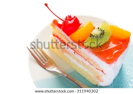 Fruit cake delicious, vanilla cake topping with fruit decorated with whipped cream and cherries with mint on dish on wood background. - stock photo