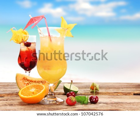 Fruit cocktail on the beach - stock photo