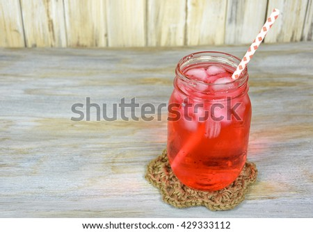 fruit drink in mason jar with gingham straw and ice cubes on rope coaster and weathered wood
