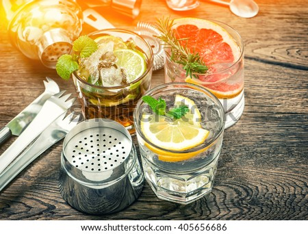 Fruit drinks with ice. Cocktail making bar tools. Vintage toned picture - stock photo
