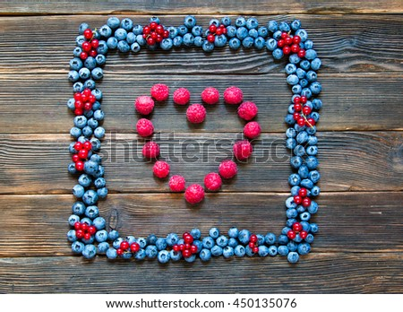 Fruit frame of blueberries and red currants with heart of raspberries. Tasty summer fruits. Top view. Rustic style. Mix of different berries - stock photo