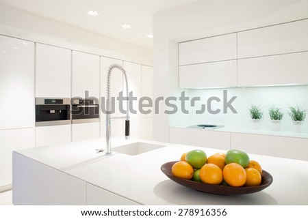 Fruit in a bowl on the marble island in white kitchen - stock photo