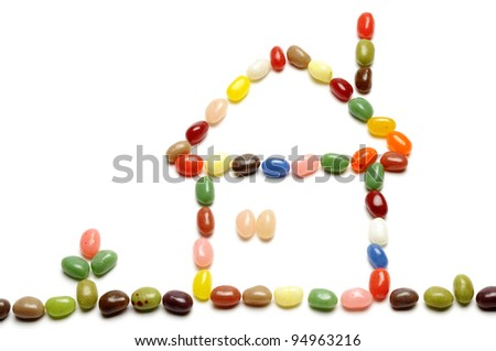 fruit jelly beans, home-shaped on white background - stock photo