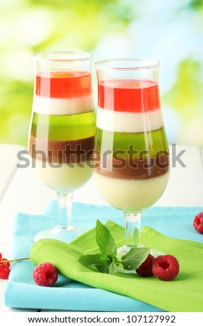 fruit jelly in glasses, berries and mint on wooden table on green background - stock photo