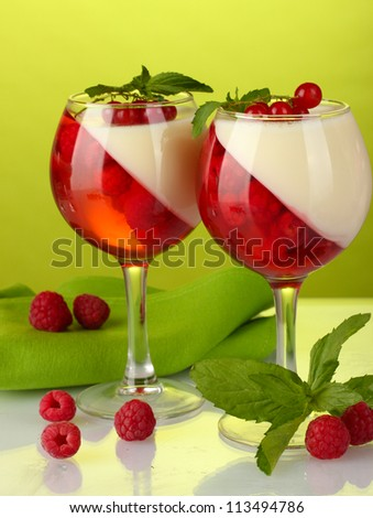 fruit jelly with berries in glasses on green background - stock photo