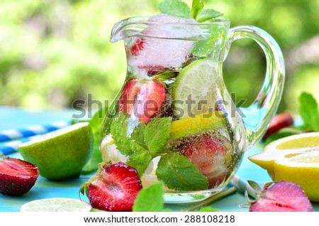 Fruit lemonade with strawberry in a pitcher on blue wooden table.