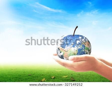 Fruit of planet in human hands over green meadow and blue sky background. Ecology, Biological City World Food Day Alternative Energy Eco Friendly CSR concept. Elements of this image furnished by NASA. - stock photo