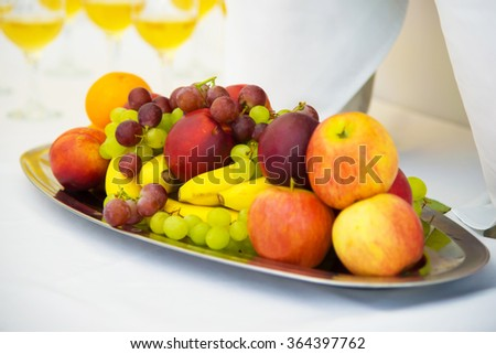 Fruit on a platter. Festive table with food. Serving. Bananas, grapes and pears and apples.  - stock photo