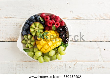 Fruit plate with variety of berries, mango and kiwi - stock photo
