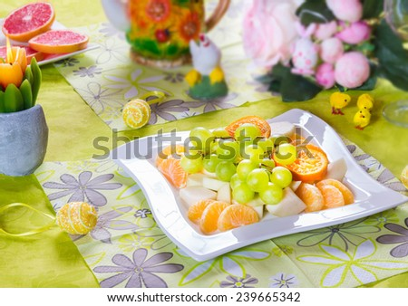 Fruit salad and colorful decorations end eggs on festive Easter table, selective focus - stock photo