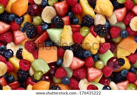Fruit salad background as fresh berries and cut fruits as blueberry blackberry strawberries melon cantaloupe raspberry pineapple banana and grapes as a symbol of healthy lifestyle and living well. - stock photo