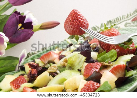 Fruit salad closeup with a strawberry on a fork, horizontal with copy space, selective focus - stock photo