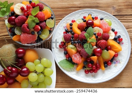 Fruit salad in a bowl and on the plate. - stock photo