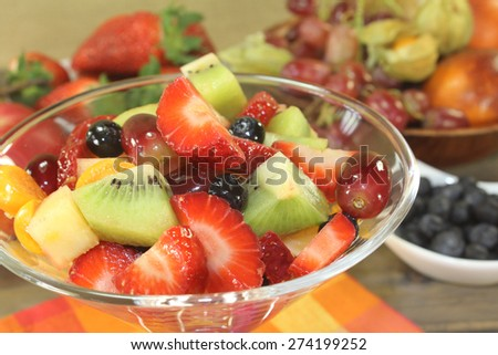 Fruit salad in a bowl on checkered napkin - stock photo