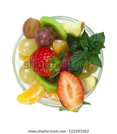 Fruit salad in a glass bowl on white background - stock photo