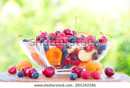 Fruit salad in a glass bowl outdoors - stock photo