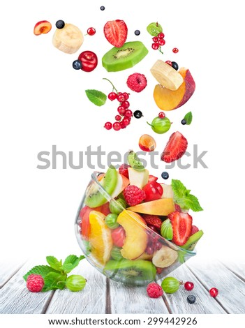 fruit salad in glass bowl with ingredients in the air on white wooden table - stock photo