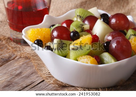 Fruit salad of oranges, grapes. pears, kiwis in a white bowl and grape juice closeup. horizontal