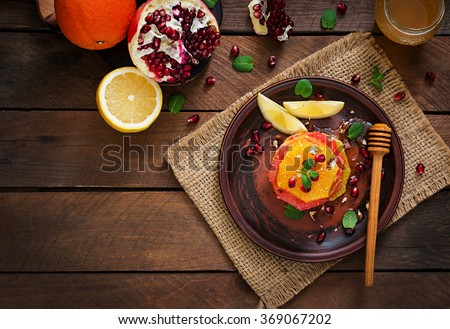Fruit salad with grapefruit and orange, pomegranate seeds, honey and lemon, decorated with mint. Top view - stock photo
