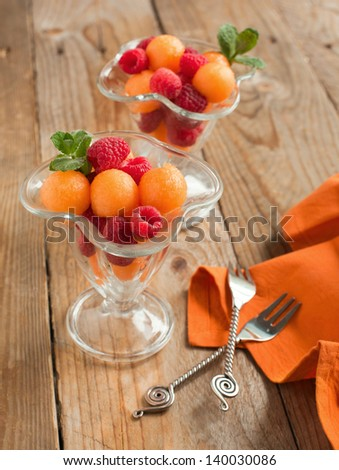 Fruit salad with melon balls and raspberries in glass bowl - stock photo