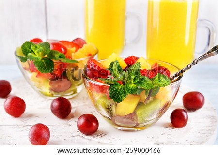 Fruit salad with mint and orange juice in glassware on color wooden background - stock photo