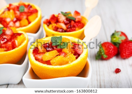 Fruit salad with pomegranate, strawberry and oranges in hollowed-out orange. On wooden table. - stock photo