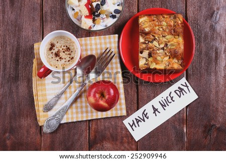 Fruit salad with yogurt, cutlery, apple pie and apple on the table. A delicious and hearty breakfast. Pastries and cappuccino. A cup of coffee on the table. Note the wish. Surprise for a loved one. - stock photo