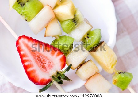 Fruit shashlik on white plate, closeup