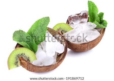 Fruit slices and ice cubes in coconut shell isolated on white. Cold drinks concept - stock photo