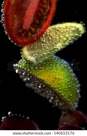 fruit slices in water coated bubbles on a dark background