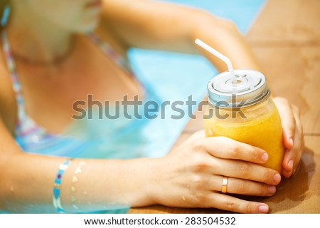 Fruit smoothie - healthy eating concept. Close up of  detox smoothie with mango. Woman hand with gold stikcer tatto holding mango smoothies outside on the pool.