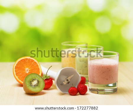 Fruit smoothie on wooden table on narural background. - stock photo