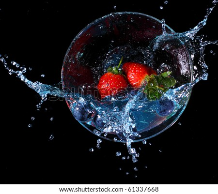 Fruit splashing into a glass of blue liquid. Concept - make a splash - stock photo