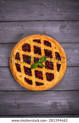 Fruit tart with cherry filling and fresh cherry and mint, top view - stock photo