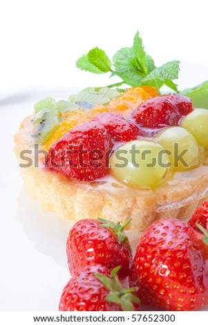 Fruit tart with strawberries, grapes and kiwi, served with mint