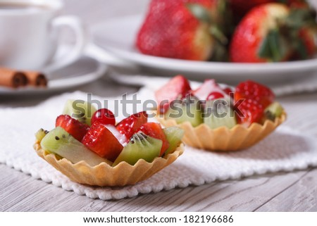 fruit tartlets with strawberries and kiwi on the table closeup   - stock photo